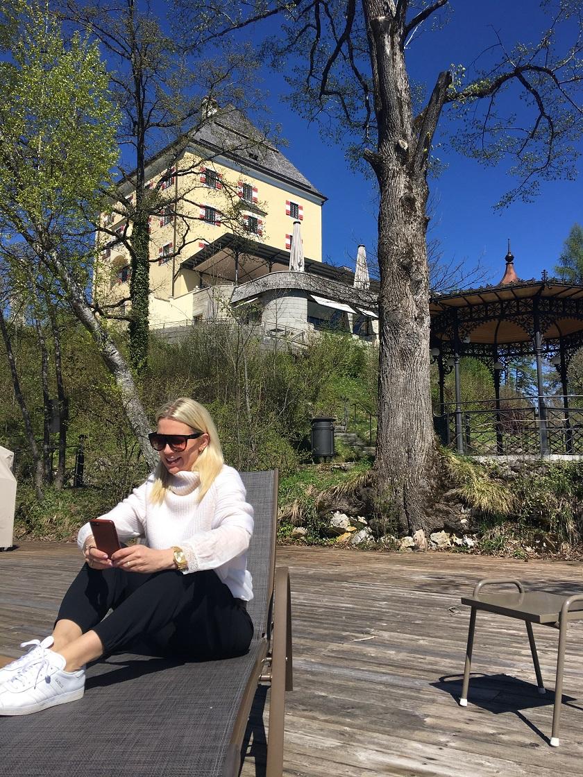 Ich auf der Liege sitzend, am Handy, im Hintergrund Schloss Fuschl